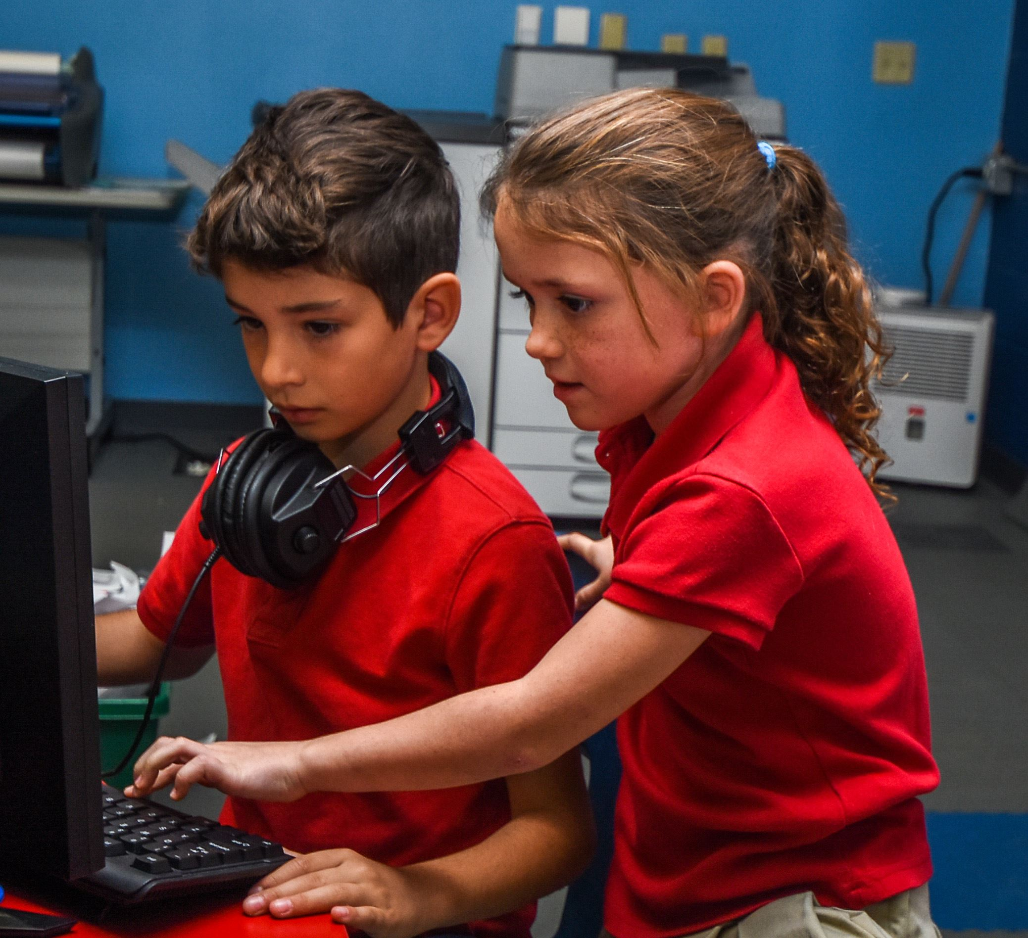 A girl assisting a boy on a computer in the STEM lab.